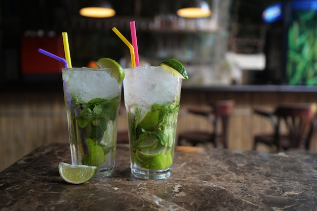 Hermosos cócteles con alcohol bebidas de mojito de lima y menta en el bar