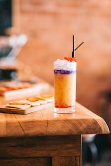Hermosos cócteles alcohólicos en barra de bar de madera y bocadillo de queso