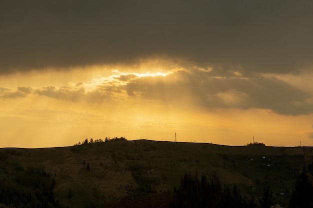 Hermosos colores del atardecer sobre las montañas de los cárpatos, ucrania, europa. puesta de sol después del caluroso día de verano. foto en tonos naturales naranja y azul.