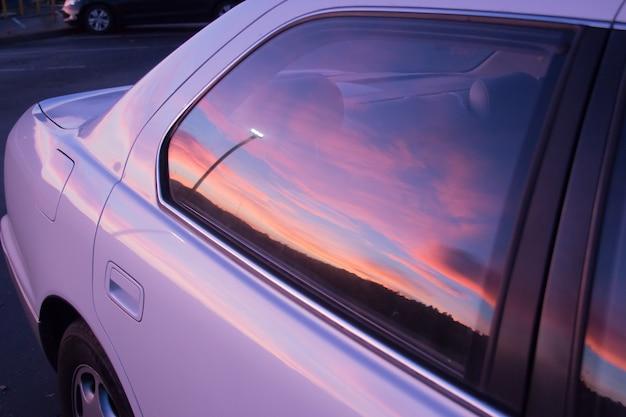 Hermosos colores del cielo del atardecer reflejados en la ventana de un automóvil púrpura