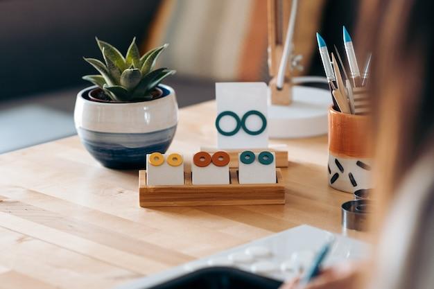 Hermosos y coloridos aretes hechos con arcilla por un artesano no reconocido colocados en una mesa de madera.