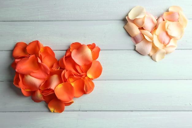 Hermosos corazones de pétalos de rosa en madera