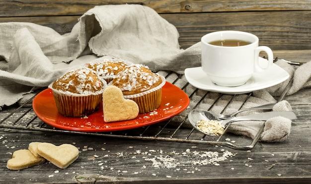 Hermosos cupcakes con bayas sobre fondo de madera en placa roja