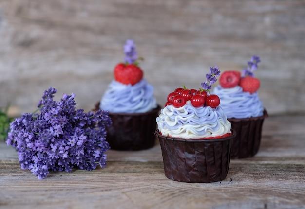 Hermosos cupcakes caseros con crema de queso morado, decorados con bayas de grosella, frambuesa y fresa, y un ramo de lavanda