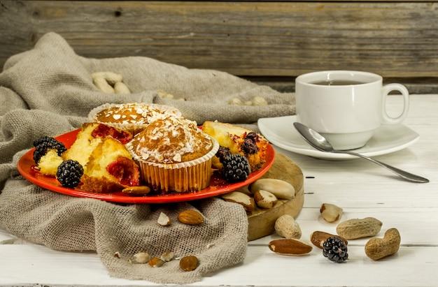 Hermosos cupcakes con frutas del bosque en mesa de madera en placa roja