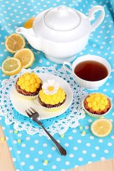 Hermosos cupcakes de limón y té aromatizado en primer plano de la mesa de comedor
