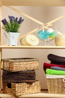 Hermosos estantes blancos con diferentes objetos relacionados con el hogar, en la superficie de la pared de color