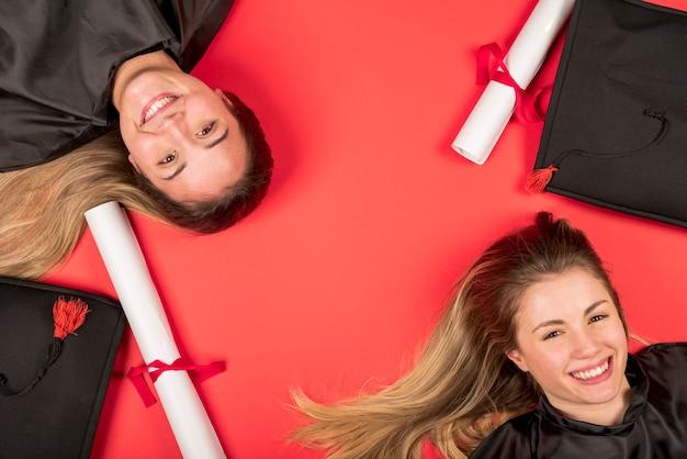 Hermosos graduados con fondo rojo