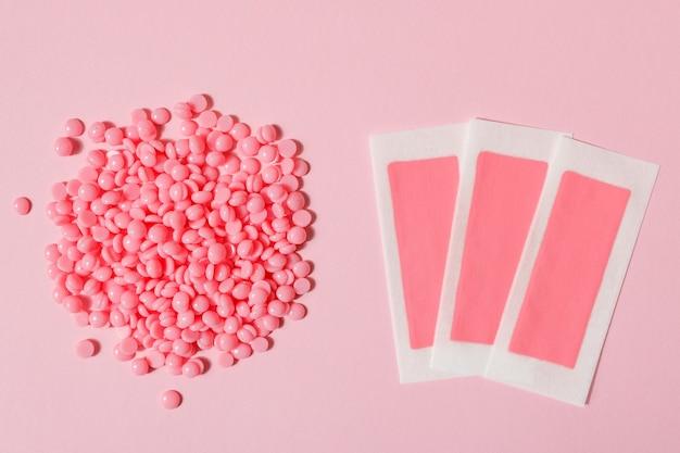 Hermosos gránulos de cera depilatoria rosa y tiras de cera para depilación sobre un fondo rosa