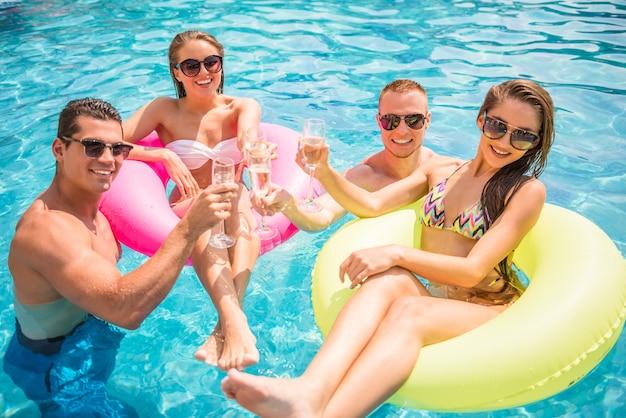 Hermosos jóvenes divirtiéndose en la piscina.