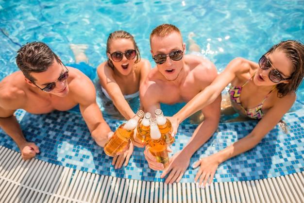 Hermosos jóvenes sonrientes y bebiendo cerveza.