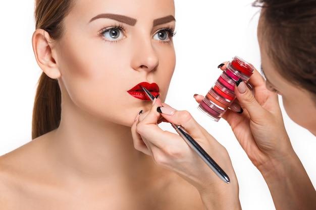 Hermosos labios femeninos con maquillaje y pincel en blanco. proceso de trabajo del artista de maquillaje