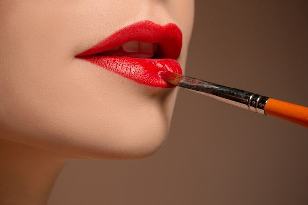 Hermosos labios femeninos con maquillaje y pincel