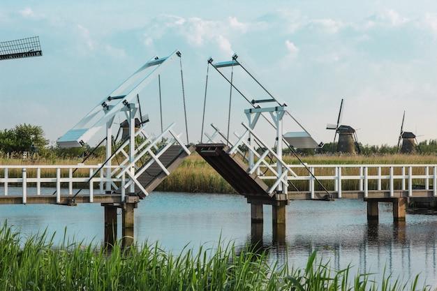 Hermosos molinos de viento holandeses tradicionales cerca de canales de agua con puente levadizo