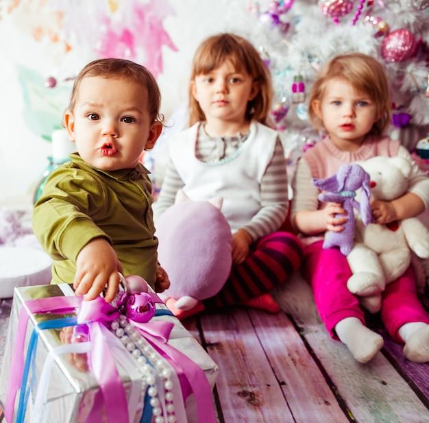Los hermosos niños sentados cerca del árbol de navidad