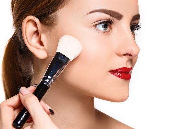 Hermosos ojos femeninos con maquillaje y pincel en blanco