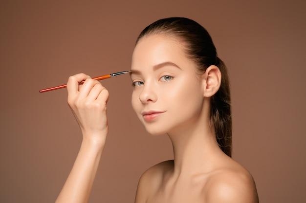 Hermosos ojos femeninos con maquillaje y pincel