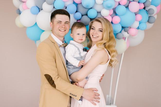 Hermosos padres jóvenes sonríen con su hijo de un año en globos rosas y azules. aspecto familiar. feliz cumpleaños fiesta