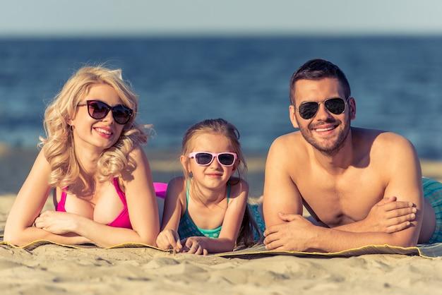 Hermosos padres jóvenes y su hija en la playa.