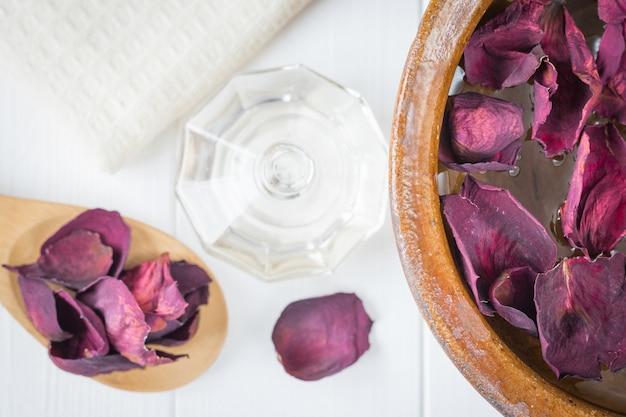 Hermosos pétalos de rosa y un tazón de arcilla