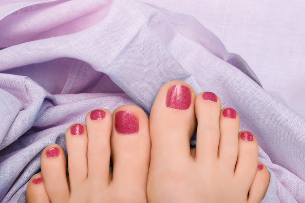 Hermosos pies femeninos con pedicura rosa brillo