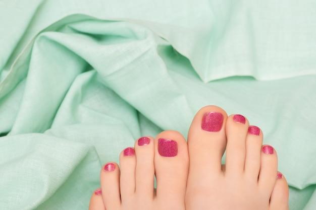 Hermosos pies femeninos con pedicura rosa brillo