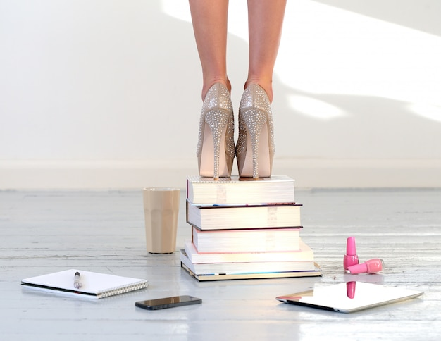 Hermosos pies en libros apilados