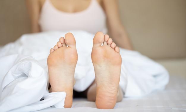 Hermosos pies de una mujer joven acostada en la cama de cerca
