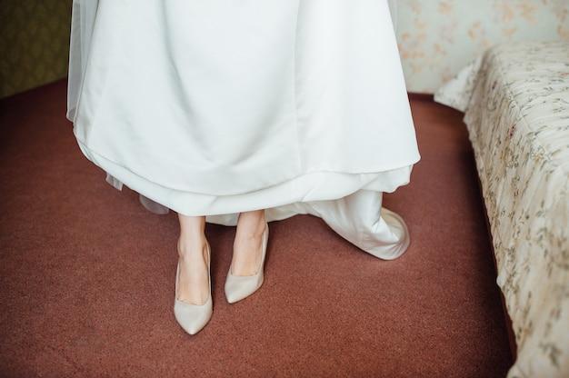Hermosos pies de novia en zapatos y vestido blanco