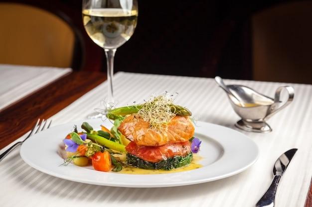 Hermosos platos para servir en el restaurante, pescado rojo salmón con verduras en un plato blanco en un restaurante sobre un fondo negro con vino blanco stokanom