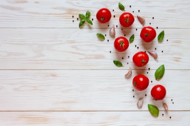 Hermosos tomates crudos frescos, albahaca y ajo.