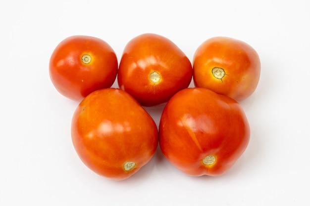 Hermosos tomates rojos frescos aislados en blanco