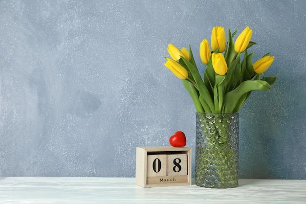 Hermosos tulipanes amarillos en un florero de vidrio en blanco para el día de la madre. espacio para texto