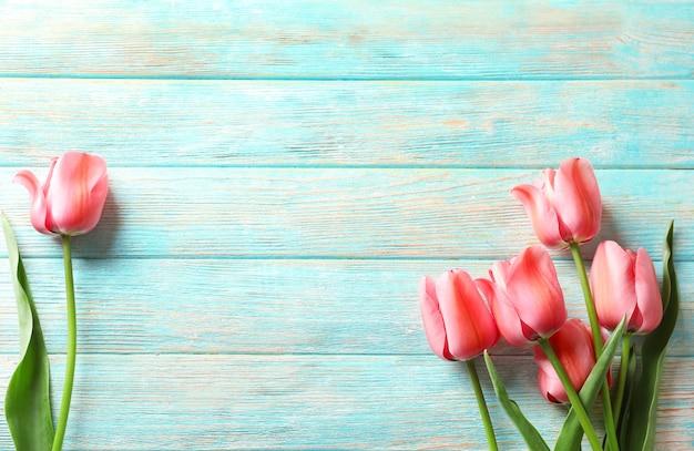 Hermosos tulipanes en el fondo de la mesa de madera
