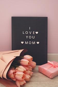 Hermosos tulipanes con la letra i love mom en letrero de letrero. fondo rosa, marco, borde. preciosa tarjeta de felicitación con tulipanes para el día de las madres, bodas o conceptos de eventos felices.