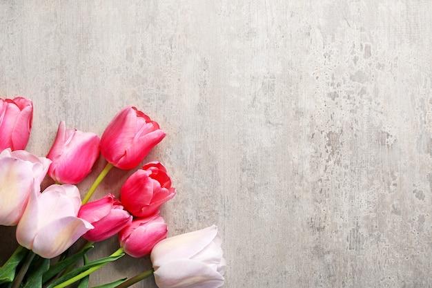 Hermosos tulipanes sobre fondo gris