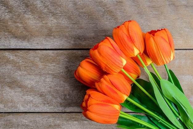 Hermosos tulipanes sobre fondo de madera