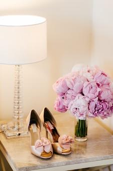 Hermosos zapatos con tacones altos, lámpara y ramo con flores de color rosa de pie en la mesita de noche.