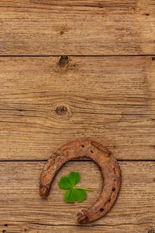 Herradura de caballo de hierro fundido muy antigua, hoja de trébol fresco. símbolo de buena suerte, concepto del día de san patricio