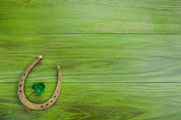 Herradura y trébol sobre fondo de madera verde. trébol verde de cuatro hojas. símbolo del día de san patricio.