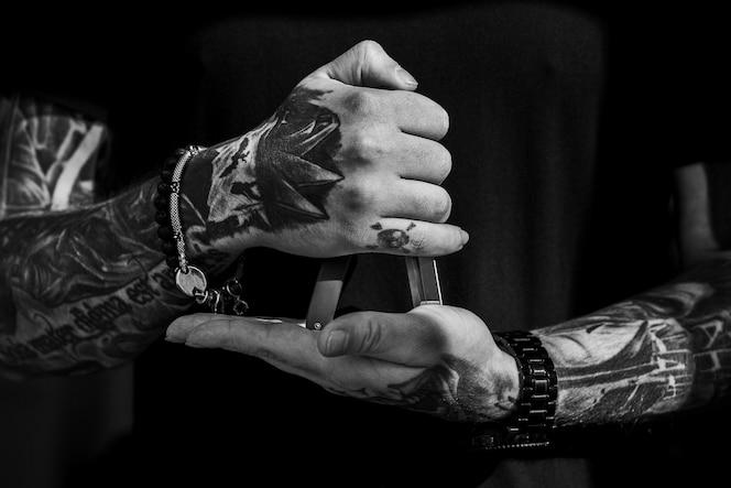 Herramienta de corte de pelo en manos de tatuajes del hombre