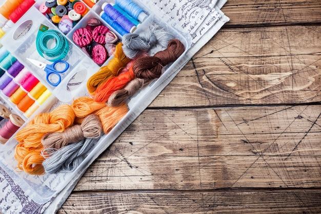 Herramienta de costura para hilos de colores, centímetros y botones con un par de tijeras sobre la mesa.
