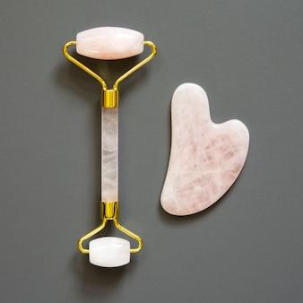 Herramienta de masaje pink gua sha. rodillo de cuarzo rosa. cuidado facial de la piel en el hogar, terapia antienvejecimiento y lifting. vista superior.