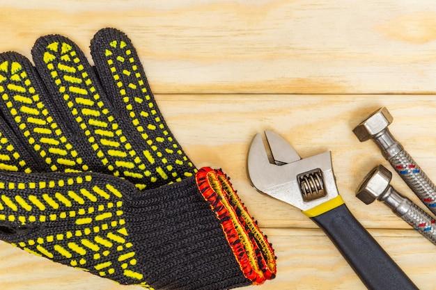 Herramienta de reparación de equipos de fontanería llave ajustable y manguera, guantes, conexión flexible sobre tablas de madera