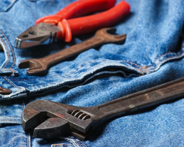 Herramienta de trabajo en blue jeans. alicates, llave, llave ajustable