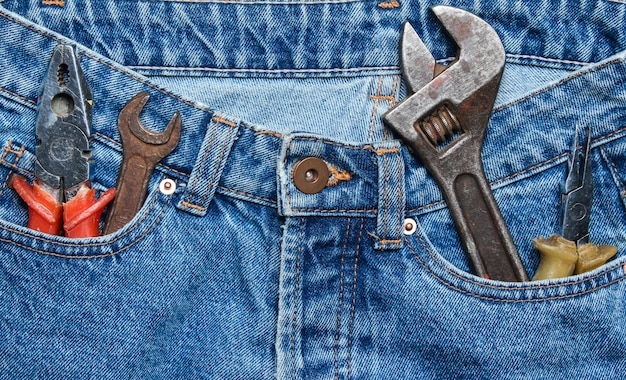 Herramienta de trabajo en el bolsillo de blue jeans. alicates, llave, llave ajustable