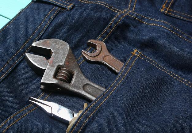 Herramienta de trabajo en el bolsillo trasero de los jeans. alicates, llave, llave ajustable