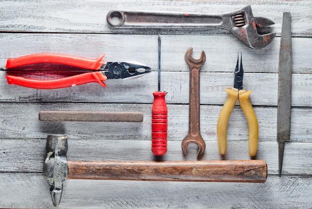Herramienta de trabajo sobre un fondo blanco de madera: destornillador, alicates, chatarra, martillo, pinzas, lima, llave ajustable. vista superior.