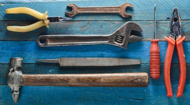 Herramienta de trabajo sobre un fondo de madera azul: destornillador, alicates, chatarra, martillo, pinzas, archivo, llave ajustable. vista superior.