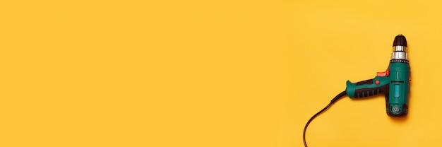 Herramienta de trabajo de taladro eléctrico sobre un fondo amarillo con espacio de copia.